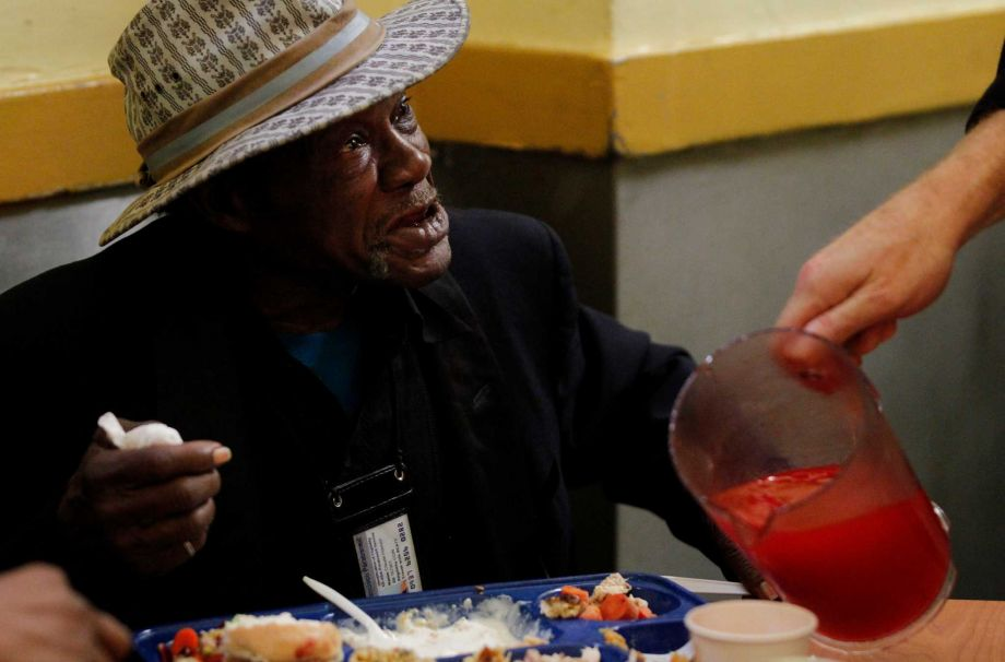 Claude Holman reacts as he receives more juice while eating his meal at Glide Memorial Church during their annual Thanksgiving dinner Nov. 27, 2014 in San Francisco, Calif. The church served nearly 5,000 Thanksgiving meals to people in the community throughout the day.