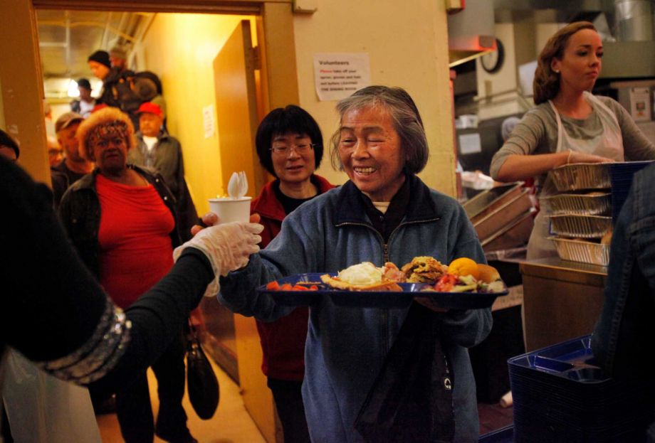 Yiau smiles as she receives plasticware with her meal at Glide Memorial Church during their annual Thanksgiving dinner Nov. 27, 2014 in San Francisco, Calif. The church served nearly 5,000 Thanksgiving meals to people in the community throughout the day.