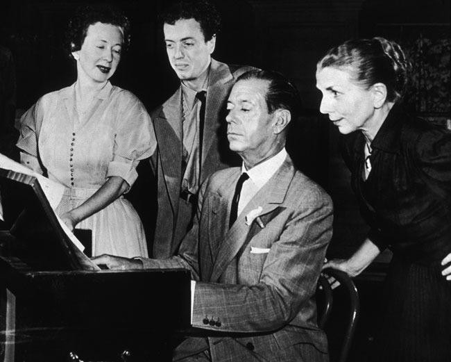 ( Photo by New York Times Co./Getty Images ) American musician and composer Cole Porter (1892-1964) plays a score for (L-R) choreographer Agnes de Mille (1905-1993), producer Saint Subber, and choreographer Hanya Holm (1893-1992), for the musical 'Out of This World'.